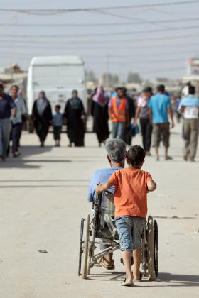 Pushing a wheelchair through the refugee camp, Northern Jordan