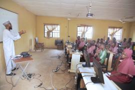 A picture of a classroom environment, with a teacher and a class on computers.