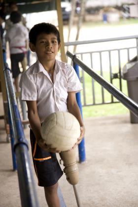 Boy walking with a football, Cambodia